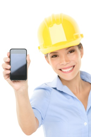 female engineer: Engineer or architect woman showing smart mobile phone copy space. Young female professional smiling friendly and happy wearing yellow hard hat isolated on white background. Multicultural woman. Stock Photo