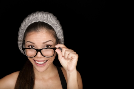 wearing glasses: Cool hipster student woman wearing eyewear glasses and knit hat isolated on black background in studio. Beautiful multiracial mixed race Asian Chinese  Caucasian female university student looking at camera smiling happy.