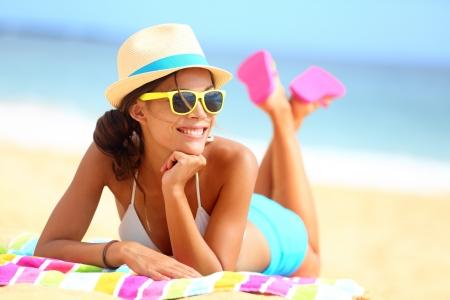 Strand vrouw funky gelukkig en kleurrijk draagt een zonnebril en strand hoed met de zomer plezier tijdens vakantiereizen vakantie. Jonge multiraciale trendy koele hipster vrouw in bikini liggend in het zand. Stockfoto