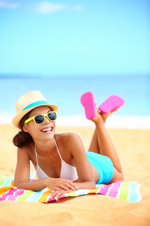 beach towel: Happy beach woman laughing having fun. Colorful lifestyle image of funky, trendy and cool young hipster girl in her twenties lying in sand enjoying summer holiday vacations. Blissful mixed race Asian  Caucasian model outdoor Stock Photo