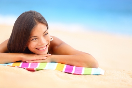 lying on side: Relaxing beach woman smiling happy looking to the side. Beautiful girl sunbathing under summer sun lying in sand on beach with blue water. Mixed race Asian Chinese  Caucasian female model.