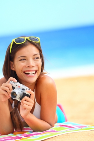 Summer beach woman fun holding vintage retro camera laughing and smiling happy during summer holiday vacation travel. Stock Photo - 17799118