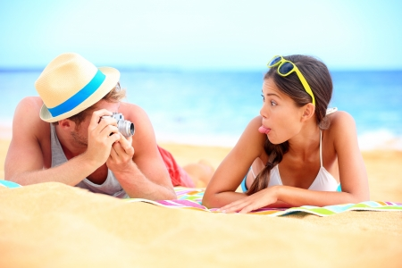 making fun: Young couple having fun on beach with vintage retro camera. Funky young interracial couple in playful lifestyle image on beach during summer holidays travel vacation. Caucasian man and Asian girl making funny face.