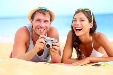 Young happy multicultural couple on beach having fun laughing during summer holiday vacation. Caucasian hipster man with retro vintage camera and asian woman joyful. Stock Photo - 17799119