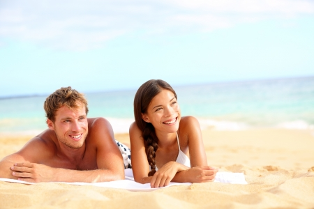 Couple on beach looking happy during summer travel vacation holidays. Multiracial young couple lying in sand on beach on looking to side. Asian woman, Caucasian man. Stock Photo