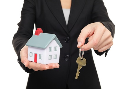Real estate agent new house keys concept. Realtor showing holding house keys and mini house model. Buying new home conceptual image with business woman in suit isolated on white background photo