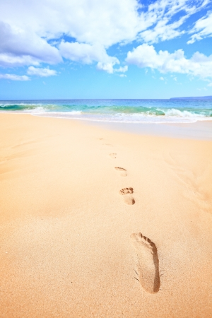 Beach travel vacation concept - footsteps in sand on beautiful sunny summer day during getaway holidays under the blue sky. From Makena beach, Maui, Hawaii photo