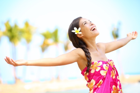 Free happy elated beach woman in freedom joy concept  Beautiful girl smiling with arms out looking up joyful on Hawaiian beach  Mixed race Asian   Caucasian girl