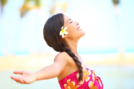 Freedom beach woman smiling happy and serene with arms outstretched in free pose  Beautiful spiritual elated happiness concept image with multicultural Asian   Caucasian female model  photo