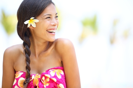 Beach woman happy looking to side laughing having fun smiling joyful and elated wearing sarong and flower on Hawaii Multiracial Asian Caucasian girl