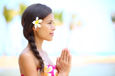 hawaiian: Serene meditation - meditating woman on beach smiling happy in profile on hawaiian beach  Beautiful portrait of mixed race Asian   Caucasian female model relaxing on Hawaii  Stock Photo