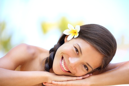 hawaiian girl: Woman natural beauty  Beautiful smiling girl outdoor portrait at massage spa  Serene happy ethnic woman relaxing looking joyful at camera  Mixed race Asian   Caucasian female model outdoors