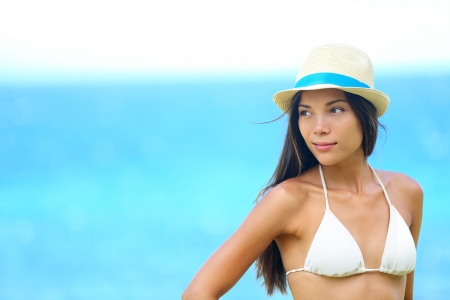 Woman beach portrait looking to side with wearing hat and beachwear bikini  Beautiful young modern multiracial female model looking serious with subtle smile  Half asian and half caucasian model outdoors  Stock Photo - 17924500
