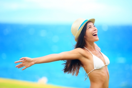 arms up: Freedom - free young woman happy on beach smiling joyful and cheerful with arms out on blue ocean sea background  Multicultural woman wearing beach hat and bikini  Stock Photo