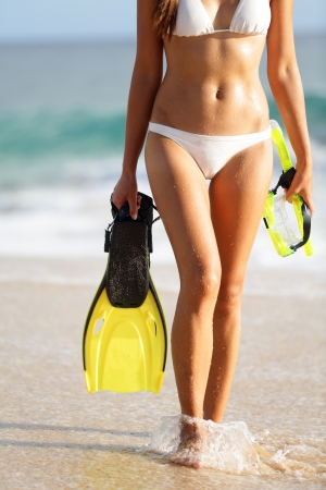 Vacation and beach holidays travel concept  Woman walking with snorkeling equipment, fins and mask, in water at sunset  Beautiful young bikini model on Makena big beach, Maui, Hawaii