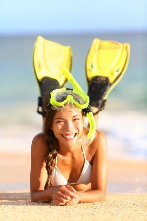 flippers: Vacaciones vacaciones de playa mujer snorkel fun mujer alegre feliz usando equipo de snorkel, aletas y m�scara, acostado en el agua y la arena mirando a la c�mara Hermosa raza mixta modelo Caucasian Asian bikini