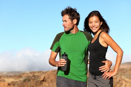 active lifestyle: Young multicultural couple outdoors in sporty outfit  Portrait after running workout outside in mountains  Asian sport fitness woman and Caucasian man models  Stock Photo