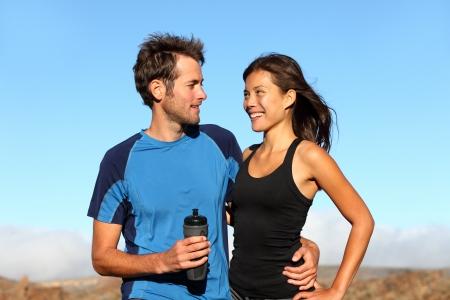 pareja saludable: Joven rom�ntico sano brazo atl�tico pareja de pie en el brazo tomando un descanso del entrenamiento en campo abierto sonrisa en las caras de cada otros. Multi�tnico pareja con la mujer asi�tica y hombre cauc�sico. Foto de archivo
