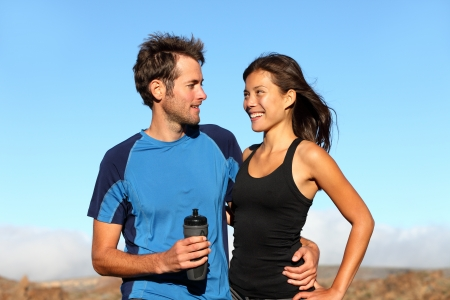 couple exercising: Young romantic healthy athletic couple standing arm in arm taking a break from training in open countryside smiling into each others faces. Multiethnic couple with Asian woman and Caucasian man.