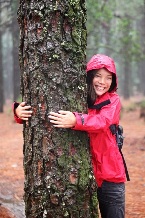strives: Happy beautiful young woman in an anorak standing hugging a tree in misty woodland as she strives to protect the environment and promote sustainability Stock Photo