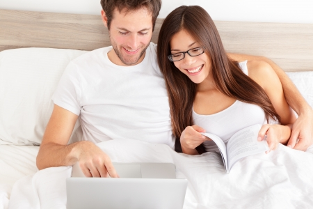 Happy affectionate young married couple sitting side by side in bed relaxing and laughing at information on the screen of their laptop  photo