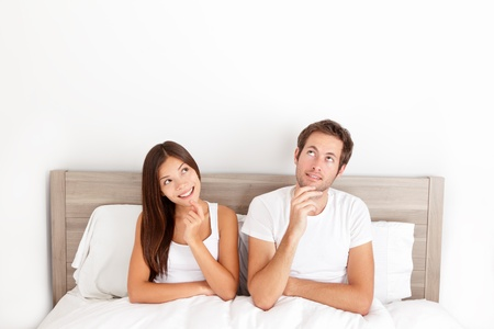 dream planning: Thinking young couple sitting pensive in bed smiling and looking up at the ceiling for inspiration and ideas Stock Photo