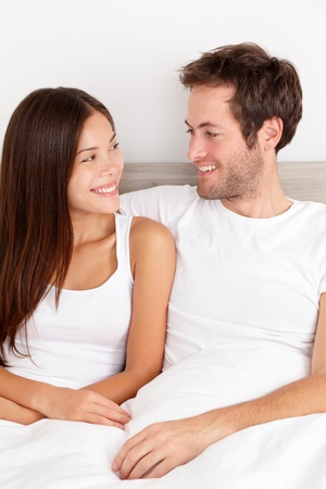 Loving young couple sitting up in the comfort of their bed looking into each others eyes and smiling happily   photo