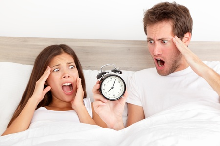 overslept: Attractive young couple missed the ringing of the alarm clock and have overslept awakening and are late
