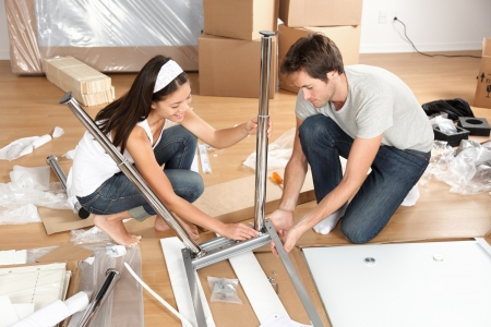 moving down: Couple moving in together assembling furniture table Stock Photo