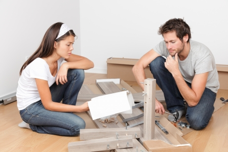 Couple moving in assembling bed furniture with problems and difficulties photo