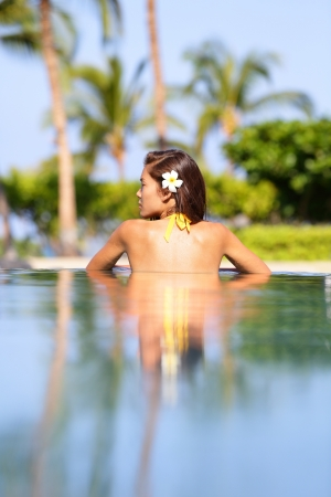 Woman relaxing in a calm tropical pool with reflections standing with her back photo