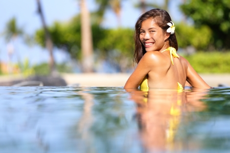 Vacation getaway woman swimming in a tropical pool  Smiling beautiful woman wearing a bikini relaxing in pool looking back over her shoulder across the inviting water at the camera  Multicultural girl photo