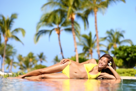 Spa resort woman enjoying a tropical vacation holiday relaxing on the edge of an infinity pool in her bikini in the summer sunshine against a background of palm trees  Mixed race Asian Caucasian woman photo