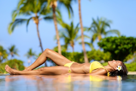 tanned: Beautiful vacation woman relaxing at a tropical spa resort lying on edge of infinity pool sunbathing in her bikini against a backdrop of palm trees  Pretty multicultural Asian Caucasian female model  Stock Photo