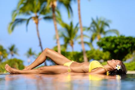 Mooie vakantie vrouw ontspannen op een tropisch kuuroord ligt aan de rand van zwembad zonnen in haar bikini tegen een achtergrond van palmbomen Pretty multiculturele Aziatische Kaukasische vrouwelijke model