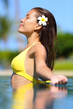 Spa woman in enjoyment meditating in water  Beautiful woman in bikini with frangipani flower in her hair standing meditating in a tropical pool with her arms outstretched and a serene expression  photo