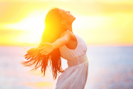 happy: Enjoyment - free happy woman enjoying sunset  Beautiful woman in a white dress embracing the golden sunshine glow of sunset with her arms outspread and face raised to the sky enjoying peace and serenity of nature Stock Photo
