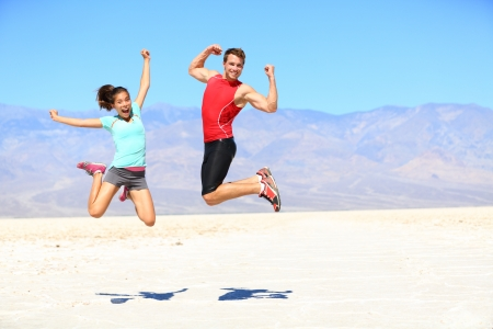 brincando: �xito - corredores j�venes que saltan emocionados celebrando y aplaudiendo feliz y lleno de energ�a en el paisaje dram�tico desierto joven alegre aptitud deportiva interracial ajuste aptitud deporte pareja, mujer, cauc�sico hombre asi�tico al aire libre