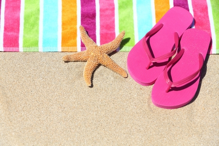 flip flops: Tropical beach vacation holiday and travel concept with a colourful striped beach towel and vibrant pink sandal flip flip thongs on pristine sand with a starfish at an idyllic coastal beach resort  Stock Photo