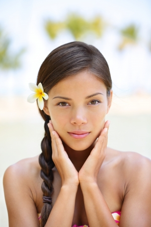 Spa woman wellness beauty woman portrait  Natural outdoors portrait of multicultural woman showing natural beauty looking at camera with flower in the hair  Mixed race Asian Caucasian girl in tropics Stock Photo - 18207176