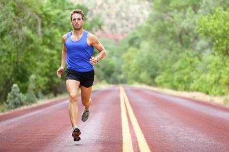 Running athlete man  Male runner sprinting during outdoors training for marathon run  Athletic fit young sport fitness model in his twenties in full body length on road outside in nature  photo