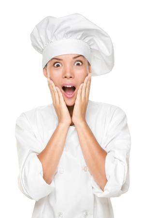 Chef-kok of bakker verrast opgewonden en geschokt Vrouw in chef uniform en hoed op zoek naar camera in shock met verbazing Mooie jonge multiculturele Aziatische blanke vrouw chef geïsoleerd op wit