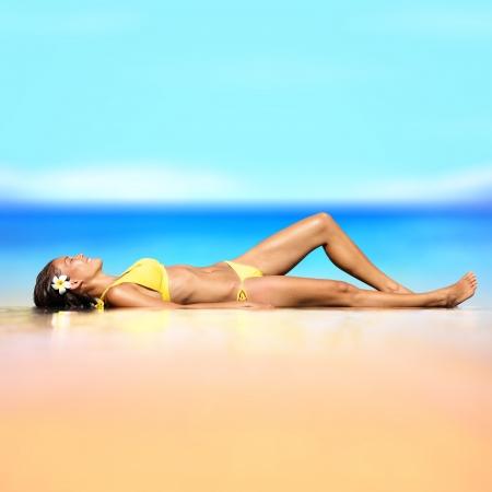 """Wakacje na plaży wakacje kobieta w bikini relaks PiÄ™kna zgrabna kobieta w bikini leżenia opalania piasek w letnim sÅ'oÅ""""cu na dziewiczy w idyllicznym tropikalnej przez turkusowy ocean Zdjęcie Seryjne"""
