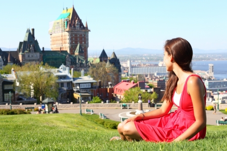 Quebec City scape with Chateau Frontenac and young woman in red summer dress sitting in grass enjoying the view Tourist or student in Quebec City, Quebec, Canada