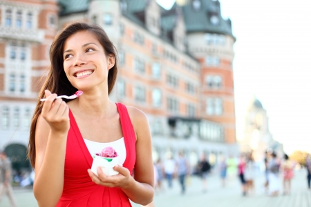 Tourist woman eating ice cream in Quebec City in front of chateau frontenac in Quebec City, Quebec, Canada  photo