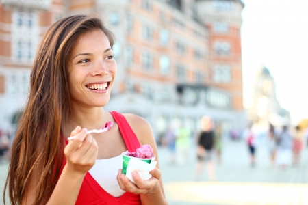 Happy tourist woman eating Ice cream in Quebec City in front of chateau frontenac in Quebec City, Quebec Canada  Smiling joyful mixed race Asian Caucasian girl enjoying holiday travel in summer dress photo