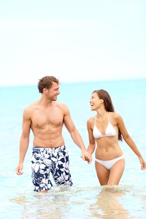 Couple on beach walking in water holding hands having fun during summer holidays travel vacation  Young happy joyful interracial couple, Caucasian man, Asian woman together outside  photo