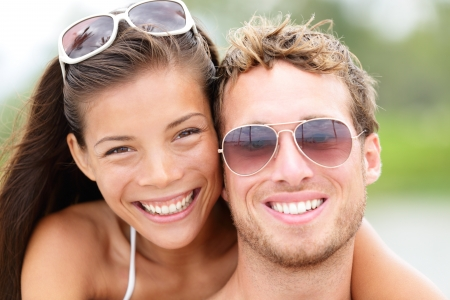 Happy young beach couple closeup portrait outdoors in sun  Young people wearing sunglasses eyewear  Joyful interracial couple, Asian woman, Caucasian man