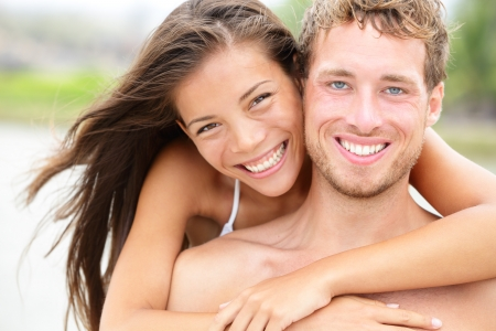 Beach couple - young happy couple portrait outdoors on beach  Smiling joyful interracial couple, Caucasian man, Asian woman on summer holidays vacation Stock Photo - 18351601