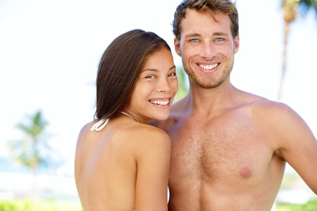 Couple beach - young multicultural people  Happy young interracial couple smiling happy looking at camera  Young asian woman and Caucasian man during summer holidays vacation under the sun  Stock Photo - 18351593